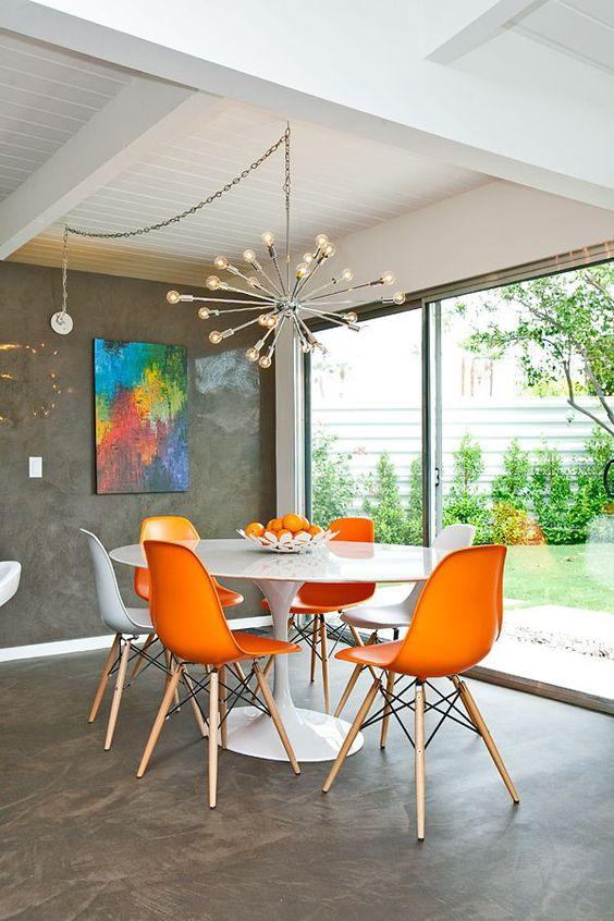 Sala de jantar cinza e laranja com mesa saarinen branca