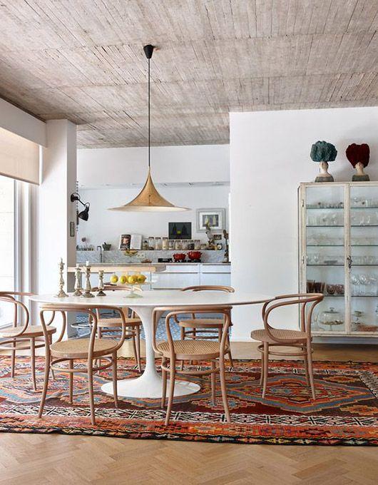 Sala de jantar com mesa saarinen branca e cadeiras de madeira