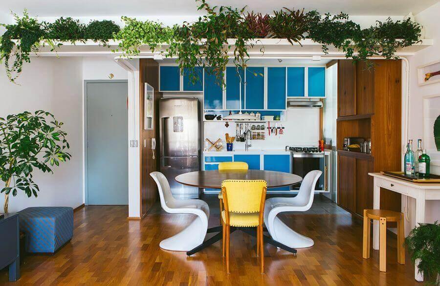 sala de jantar integrada com cozinha decorada com prateleira para plantas  Foto Histórias de Casa