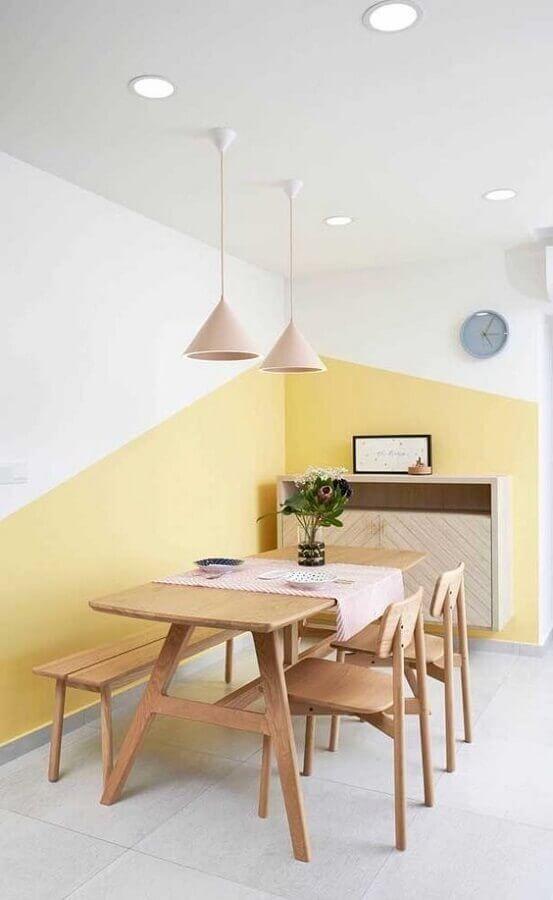 sala de jantar minimalista decorada com mesa de madeira e parede geométrica amarela e branca  Foto Jeito de Casa
