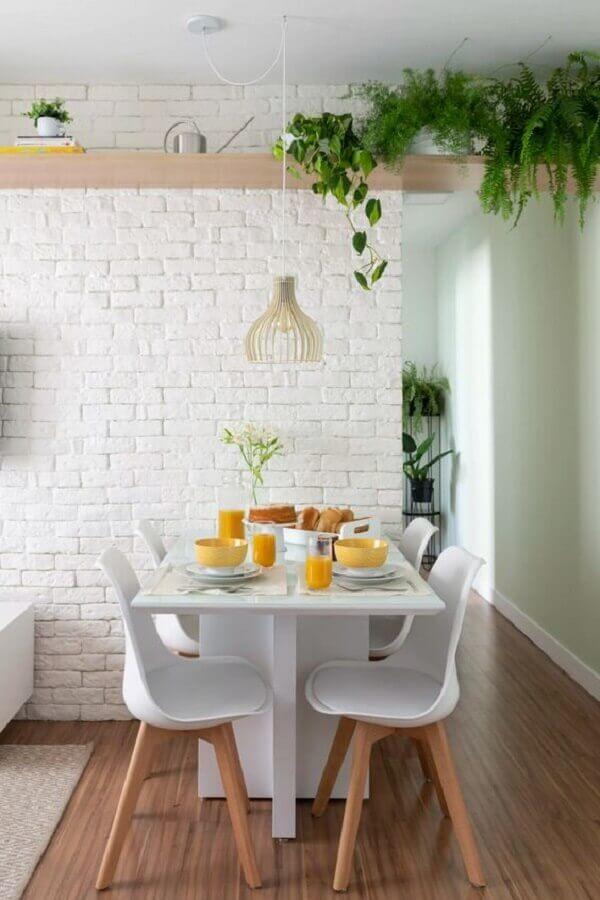 sala de jantar pequena decorada com parede de tijolinho branco e prateleira de madeira para plantas Foto Pinterest