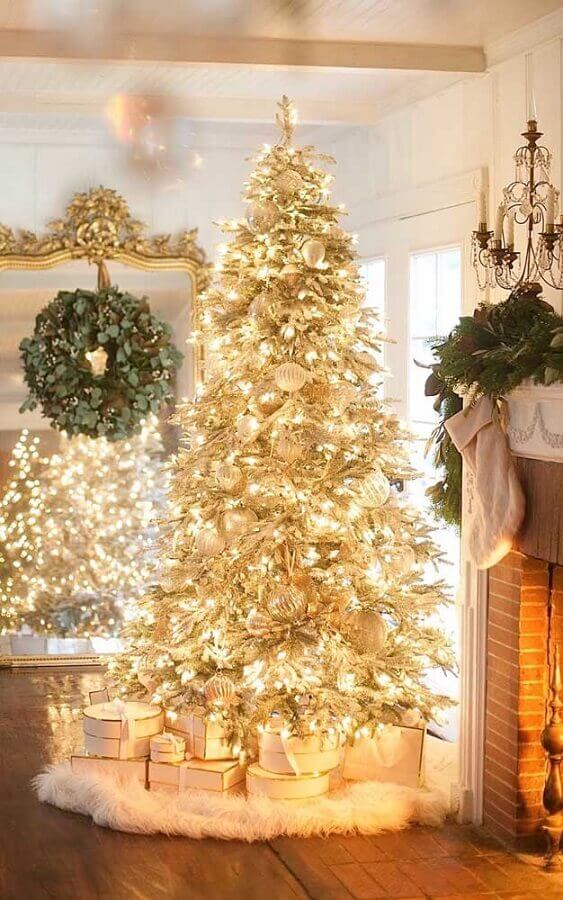 room decorated with large golden Christmas tree all lit up Photo Deavita