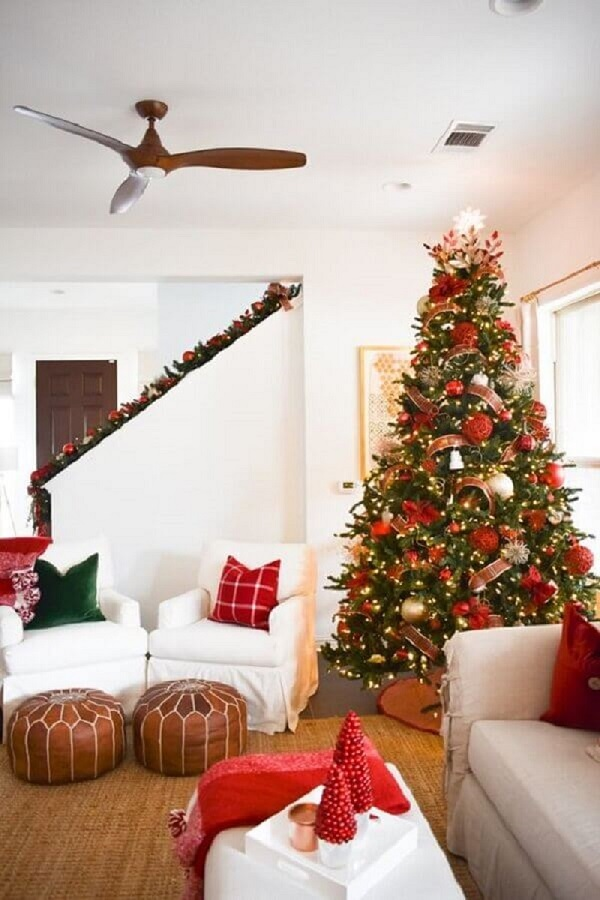 room decorated with white armchairs and large Christmas tree with red ornaments Photo Home Fashion Trend