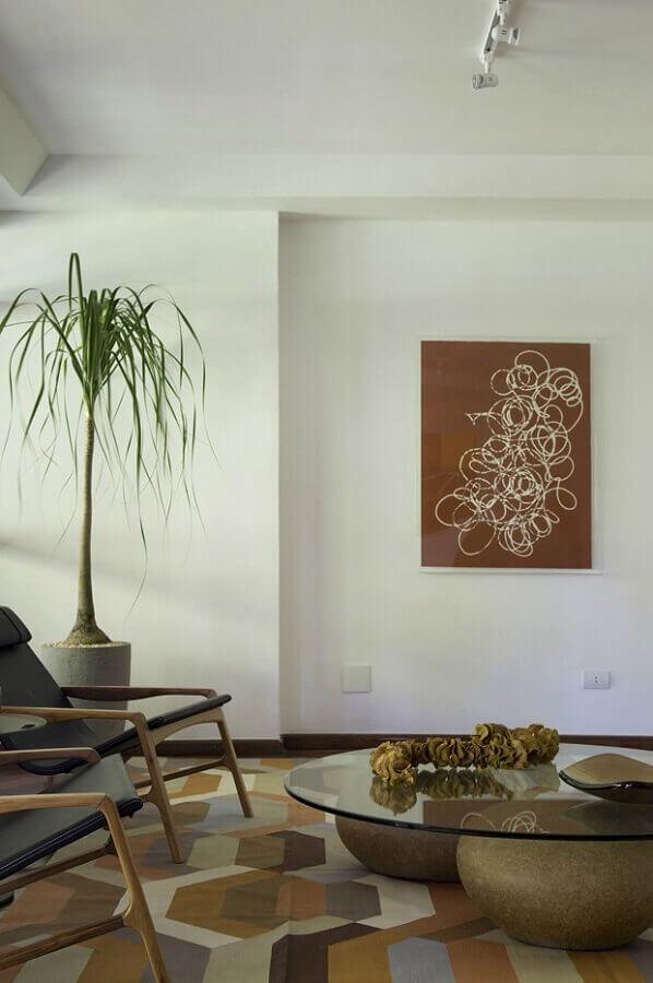 sala decorada com poltronas de madeira e tapete em tons terrosos  Foto Pinterest