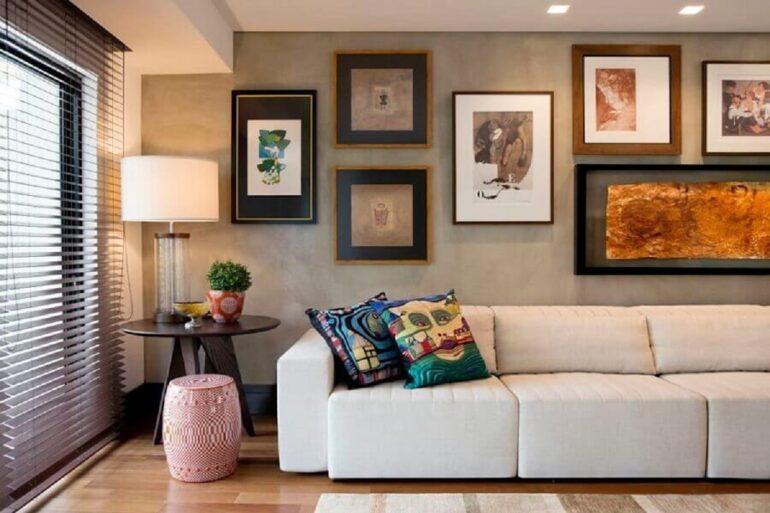 sala moderna e sofisticada decorada com sofá 3 lugares retrátil confortável e parede de cimento queimado com vários quadros Foto Elmor Arquitetura