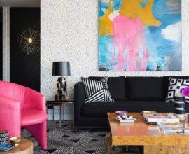 sofá preto para sala decorada com poltrona rosa e quadro grande colorido Foto Greg Natale