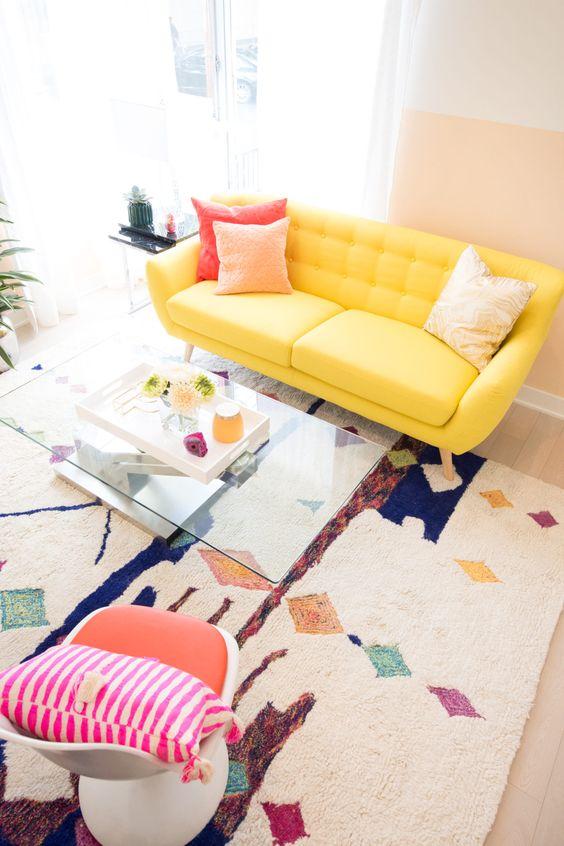 Sofá amarelo pastel com tapete colorido