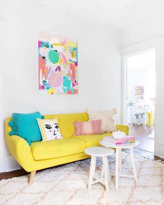 Sofá amarelo pastel com quadro e almofadas coloridas