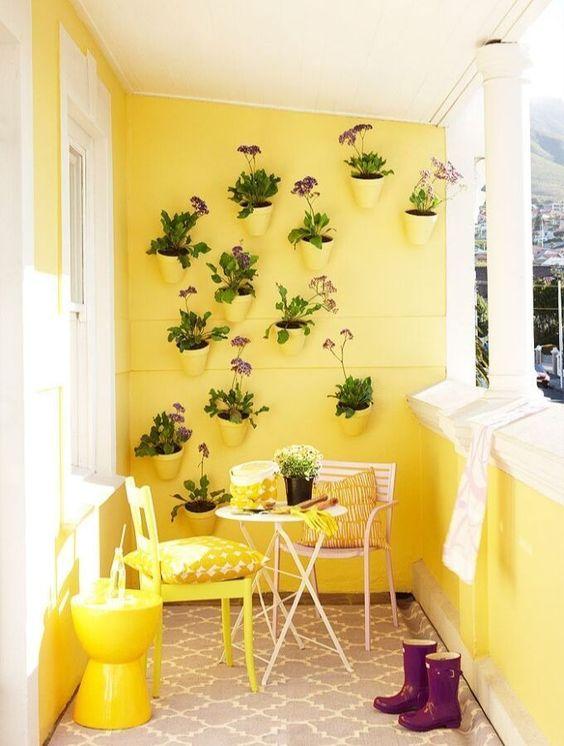 Varanda amarela com móveis em tons pasteis e plantas na decoração