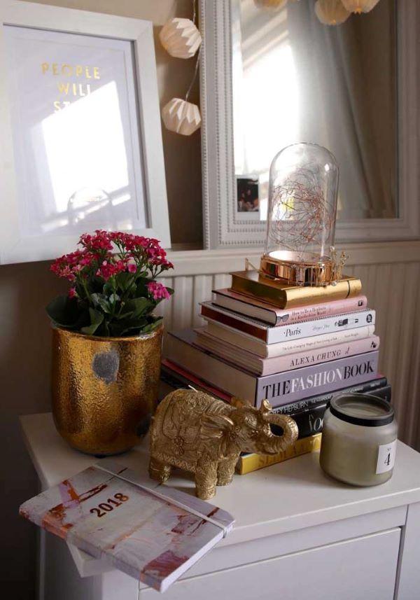 Decoração romântica com livros e vaso dourado de flor da fortuna