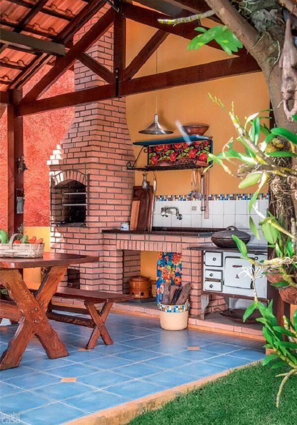 Área gourmet com fogão à lenha e churrasqueira