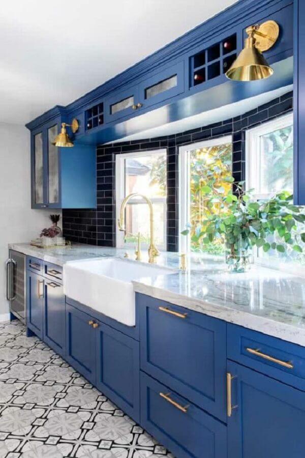 A cozinha azul e preta ganhou luminosidade na presença das janelas guilhotinas