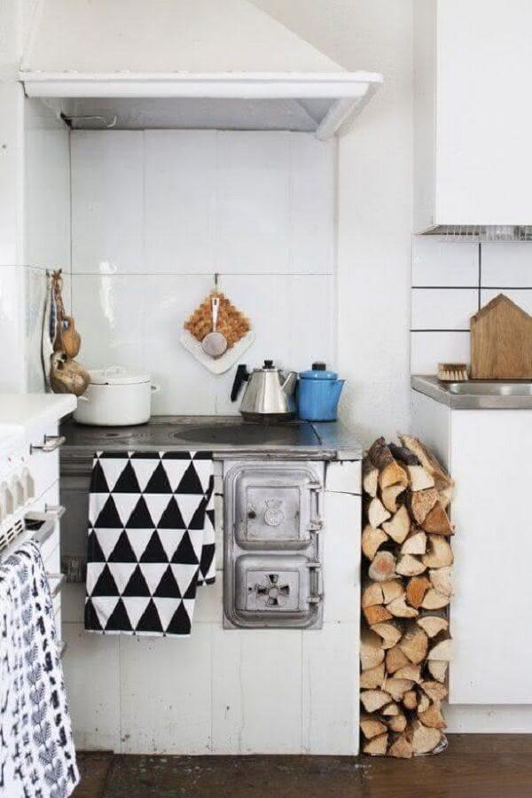 A cozinha com fogão a lenha simples ocupa um espaço especial do ambiente