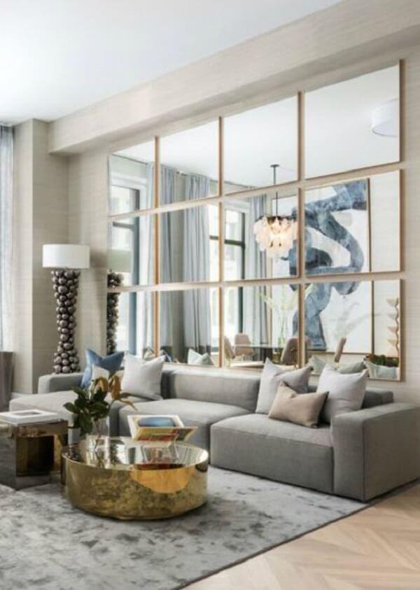 A decoração com espelho quadrado trouxe destaca para a parede atrás do sofá