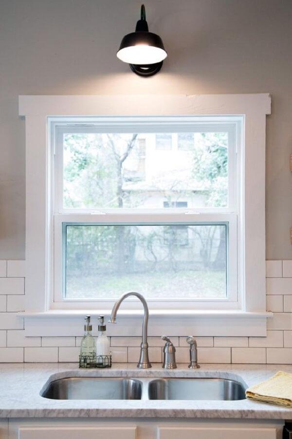 A janela guilhotina vidro fixada em frente a pia ajuda na entrada de luz natural no ambiente