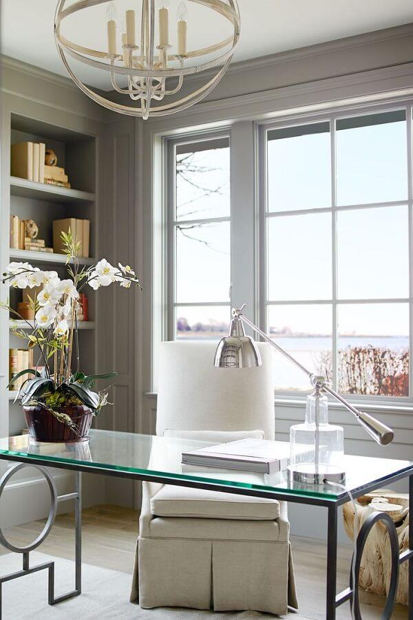 A luz natural realça ainda mais a presença de mesa de vidro para escritório