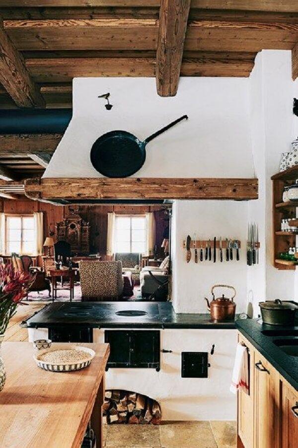 A madeira está presente em diversos elementos da cozinha com fogão à lenha