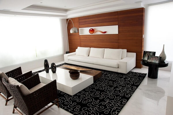 A mesa de centro branca se destaca sobre o tapete preto estampado