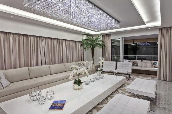 A mesa de centro em laca branca acompanha o tamanho do lustre