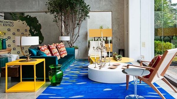 A mesa de centro redonda branca sobre o tapete azul equilibra as cores na sala