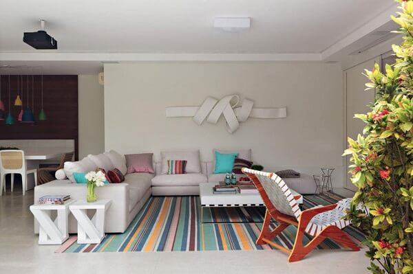 A mesa de centro retangular branca foi apoiada sobre o tapete com listras coloridas