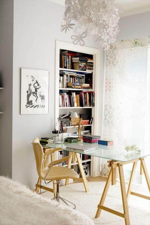 A mesa de vidro para escritório com cavalete de madeira traz um toque rústico para a decoração