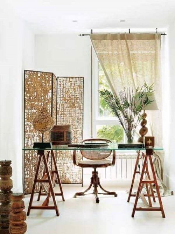 A mesa para escritório com tampo de vidro e base cavalete é a grande protagonista da decoração
