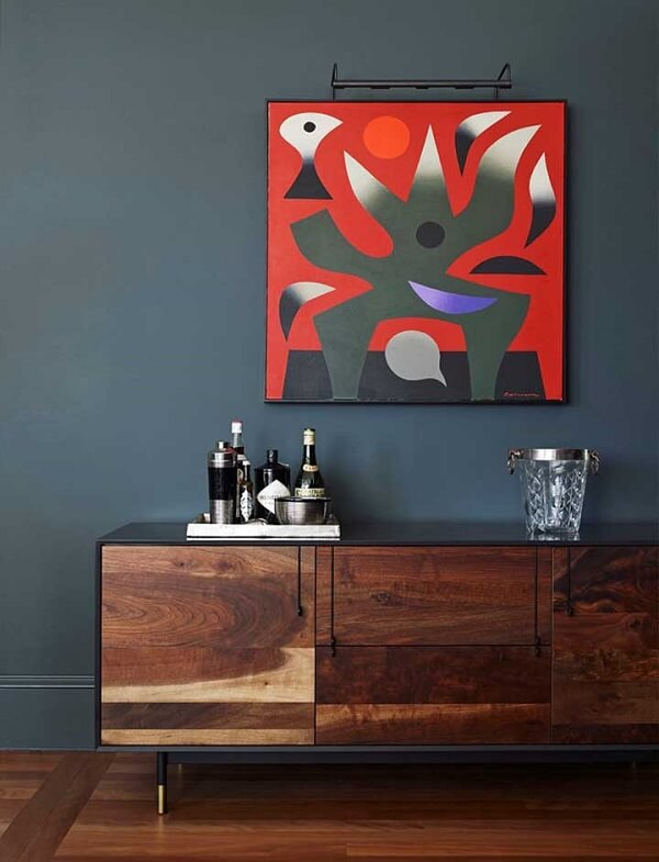 A parede azul petróleo recepciona muito bem o quadro colorido