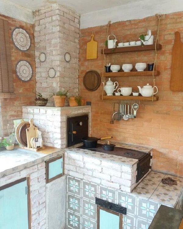 A prateleira sobre o fogão à lenha ajuda na organização de itens da cozinha