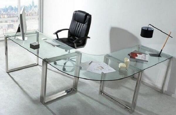 Acomode vários objetos sobre a mesa de vidro em L para escritório