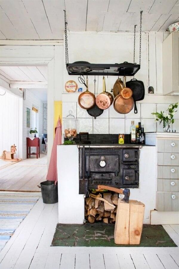 As panelas suspensas sobre o fogão à lenha trazem charme para a decoração