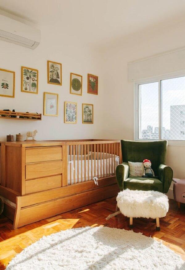 Berço com gaveta de madeira se contrasta com a poltrona verde