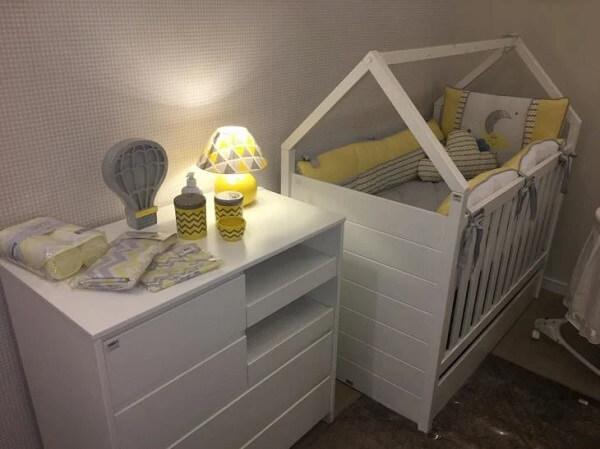 Branco e amarelo para decoração desse quarto de bebê com berço com gaveta