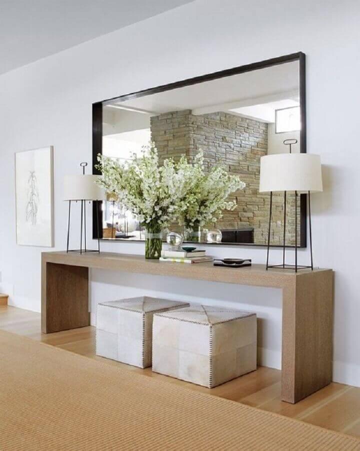Corredor decorado com aparador de madeira e espelho grande de parede  Foto We Vans