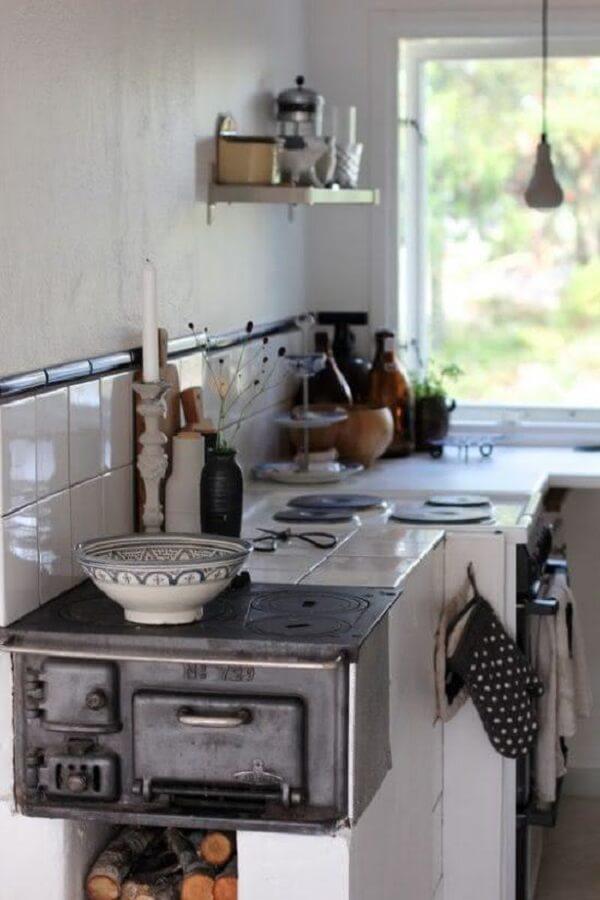 Cozinha com fogão a lenha simples e instalado na ponta da bancada