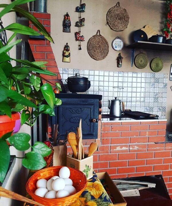 Cozinha pequena com fogão à lenha e diversos utensílios domésticos