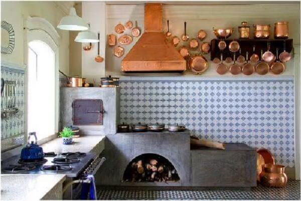 Cozinha planejada com fogão à lenha e com espaço para guardar madeira