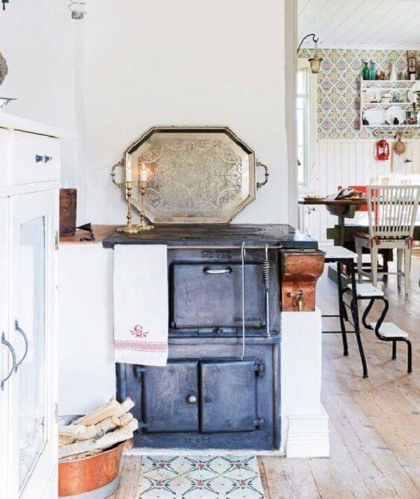 Cozinha planejada com fogão a lenha feito em estrutura de ferro