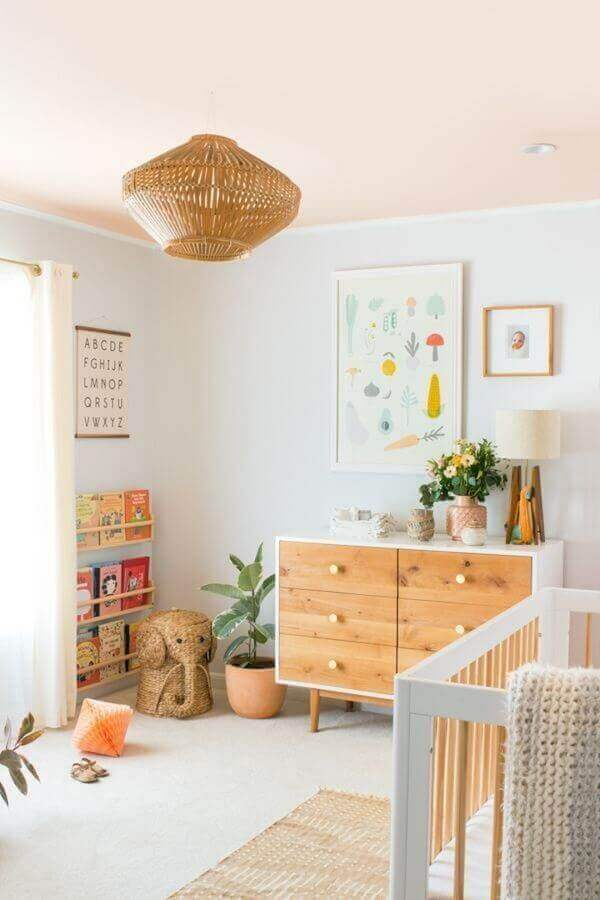 Decoração com quadros coloridos, pendente rústico e cômoda de madeira