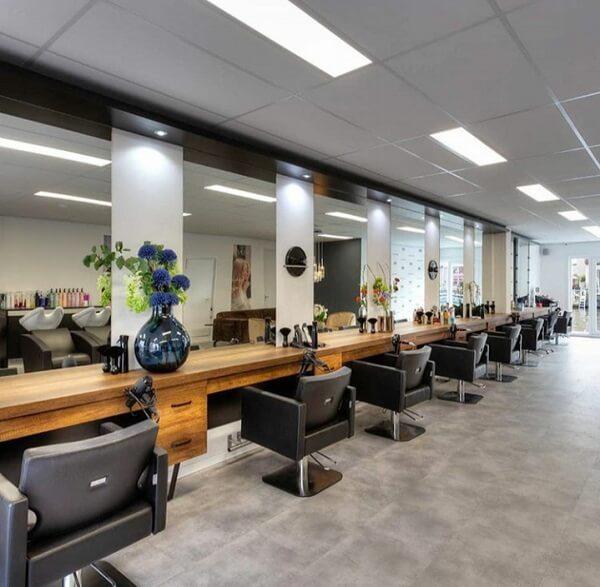 Decoração de barbearia moderna e clean acomoda vários clientes