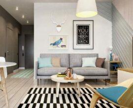 Decoração de sala com sofá cinza e tapete listrado em preto e branco