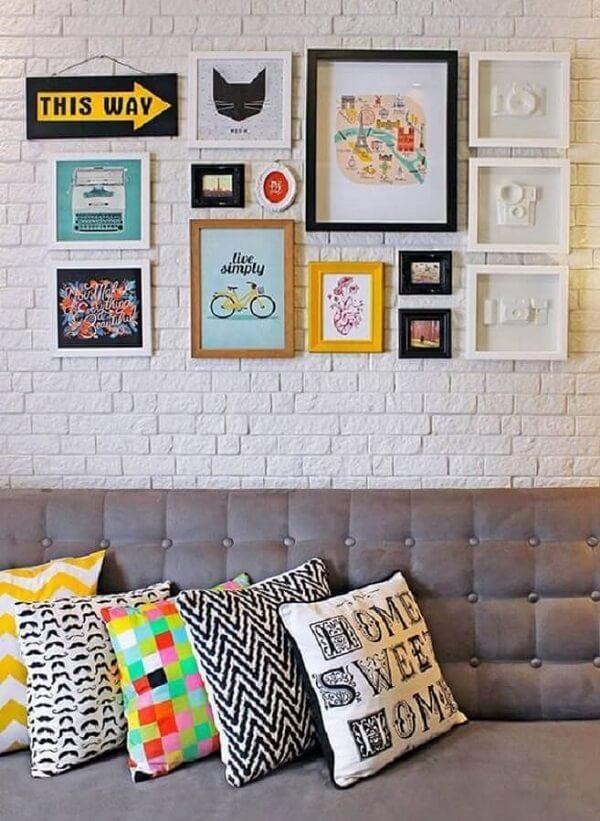 Decoração quadros coloridos fixados na parede de tijolinho branca
