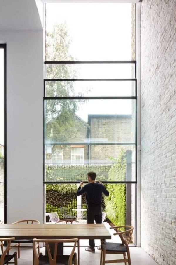 Essa janela guilhotina gigante traz beleza e funcionalidade para a sala