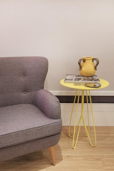 Mesa lateral amarela ao lado da poltrona cinza