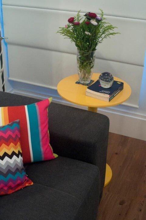 Mesa lateral alta amarela ao lado do sofá cinza