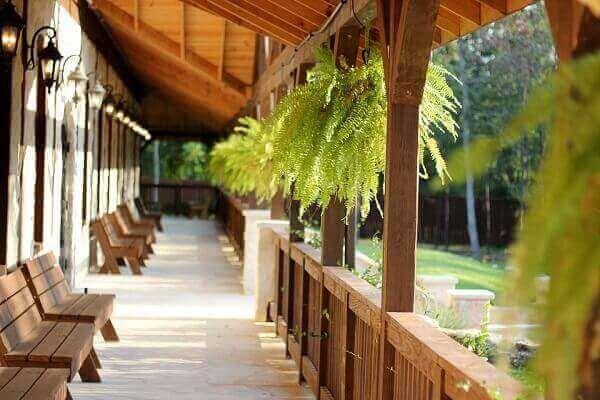 Na varanda, a samambaia foi pendurada nas vigas de madeira do telhado
