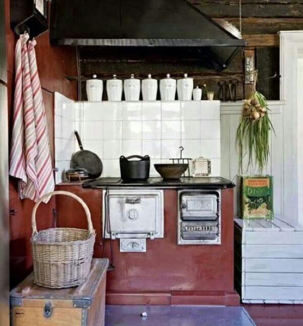O azulejo branco se destaca na cozinha com fogão à lenha