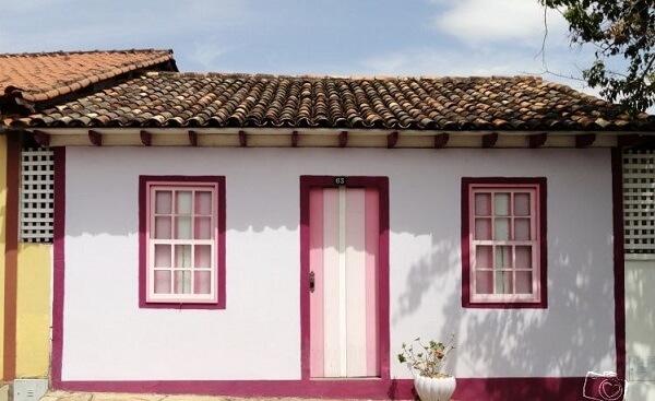 O contorno em rosa da janela guilhotina dessa casa colonial traz muito charme para a fachada