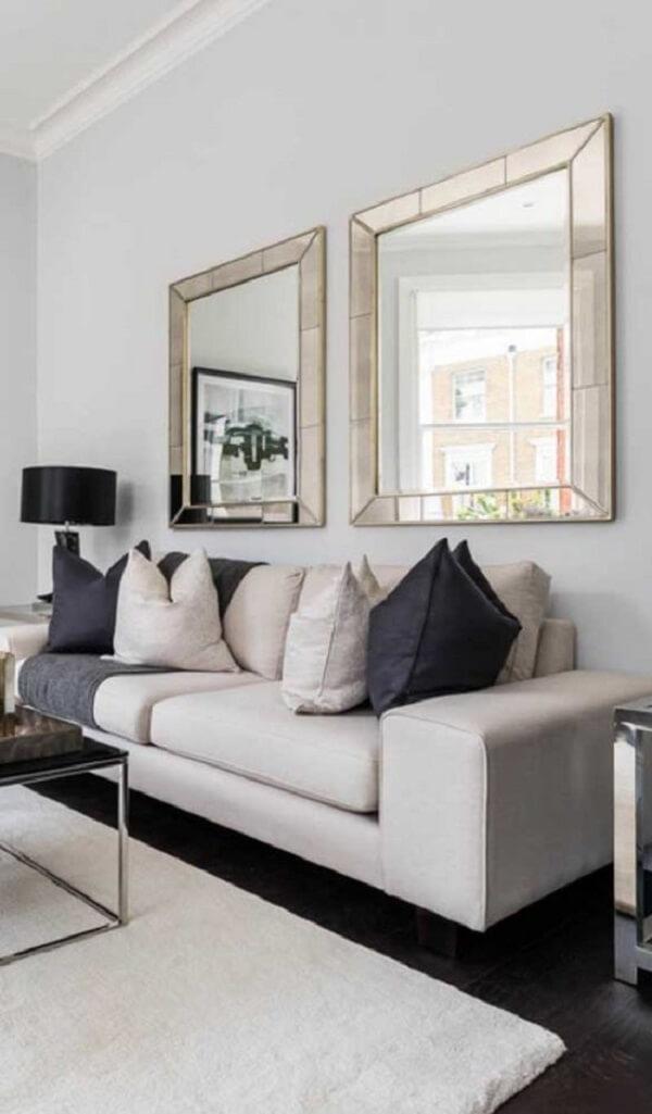 O espelho bisotado quadrado foi fixado atrás do sofá da sala de estar