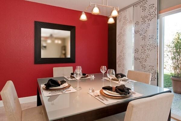 O espelho quadrado com moldura foi posicionado na sala de jantar
